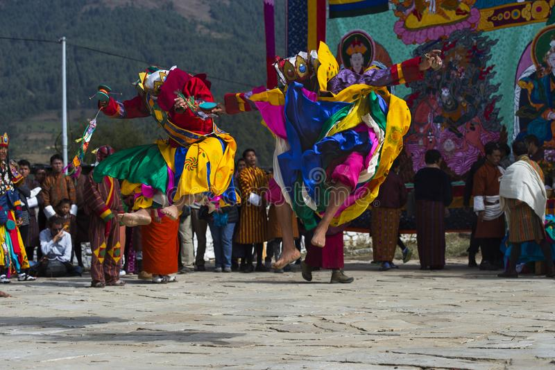 Cham dance , two dancers jump incredible high , Bumthang , central Bhutan. The main forms of dance are spectacular and theatrical masked dances called cham royalty free stock image