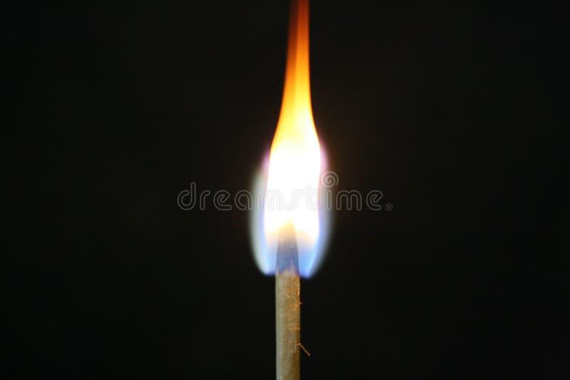 A chama de fósforo iluminou-se acima em uma sala escura foto de stock