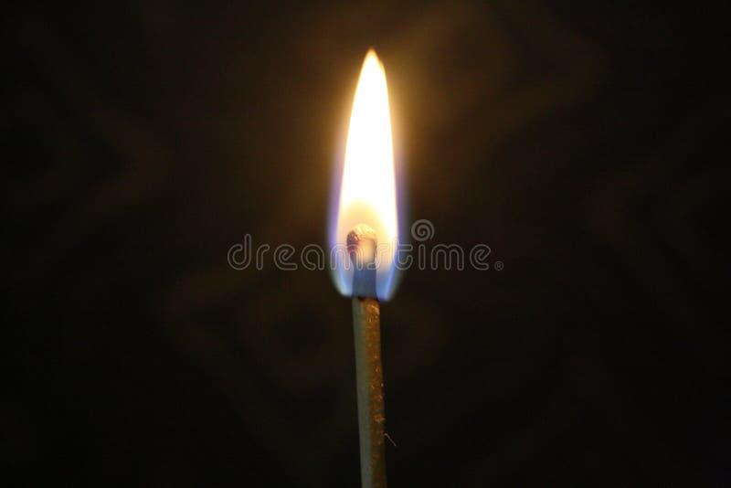 A chama de fósforo iluminou-se acima em uma sala escura fotografia de stock royalty free