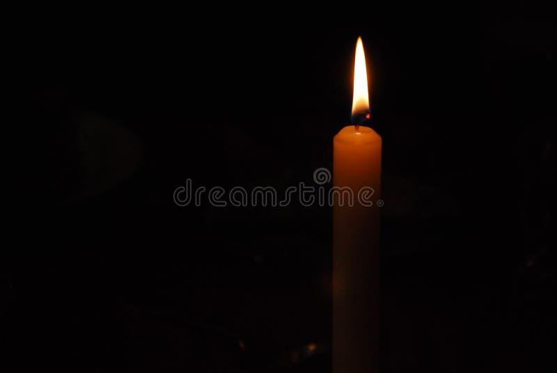 A chama de uma luz da vela na escuridão fotos de stock royalty free