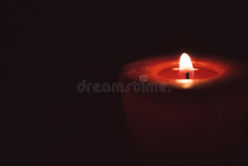Chama só que queima a vela vermelha na obscuridade imagens de stock royalty free