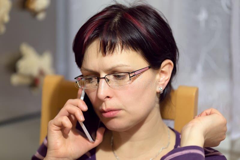 Chamada cansado da mulher pelo telefone fotos de stock
