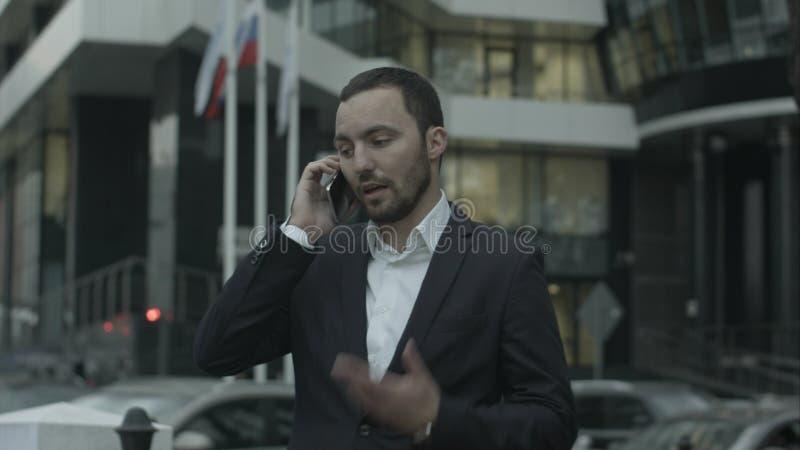 A chamada de resposta do homem de negócios do russo pelo telefone e explica algo aos sócios comerciais, eretos fora do escritório foto de stock royalty free