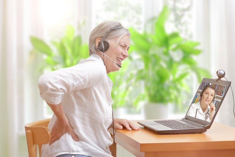 Chamada video do doutor da dor nas costas da mulher fotos de stock