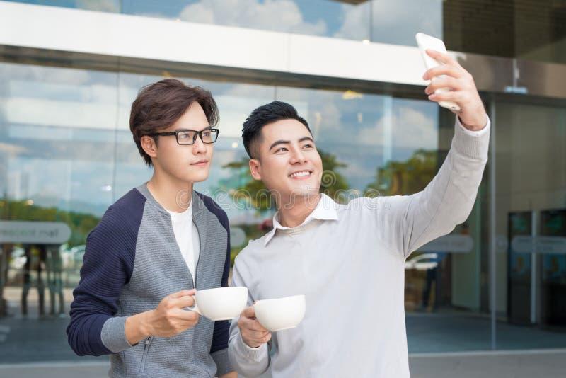 Chamada video do homem dois novo usando o smartphone fotografia de stock royalty free