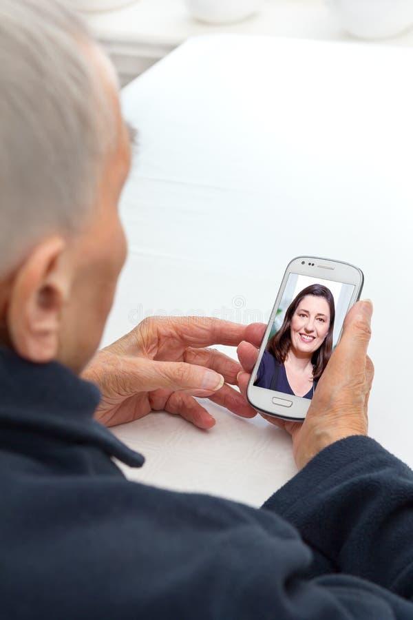 Chamada video do telefone celular da pessoa idosa fotografia de stock