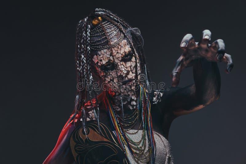 Chaman africain effrayant avec une peau criquée pétrifiée et des dreadlocks Concept de maquillage images libres de droits