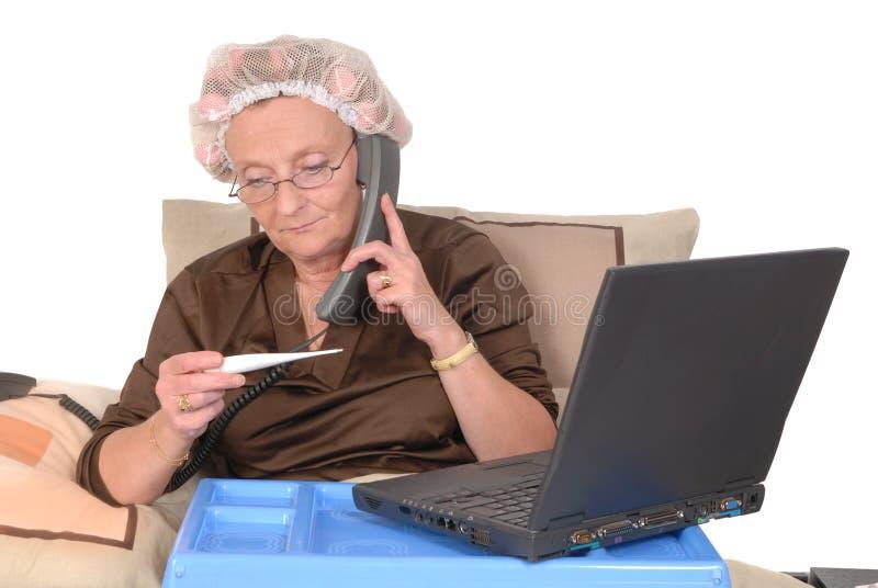 Chamando no doente, mulher na cama foto de stock royalty free