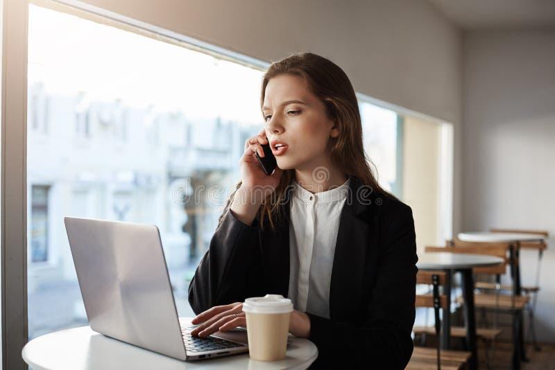 Chamando o para informar sobre a fase do trabalho Tiro interno da mulher de negócios bem sucedida séria e focalizada no equipamen imagem de stock royalty free