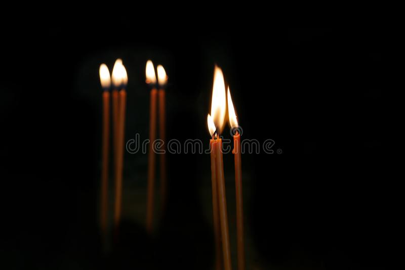 Chamas de vela em um fundo preto Velas de queimadura da oração na igreja imagem de stock