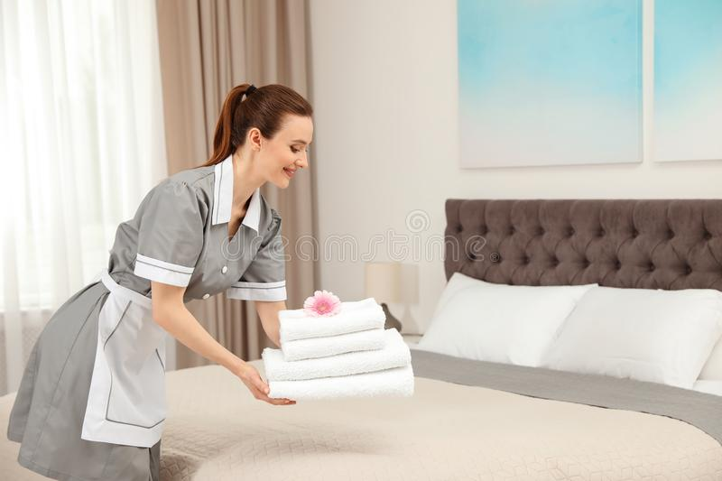 Chambermaid putting fresh towels on bed stock image