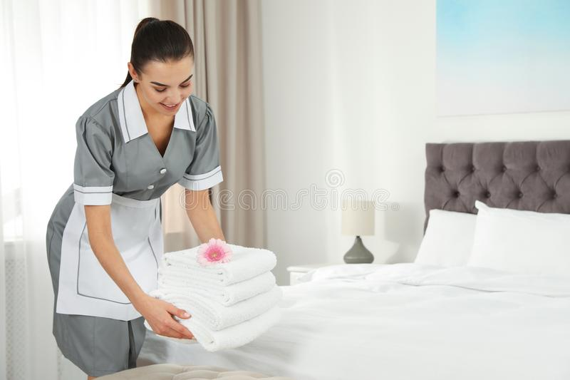 Chambermaid putting fresh towels on bed in hotel room stock image