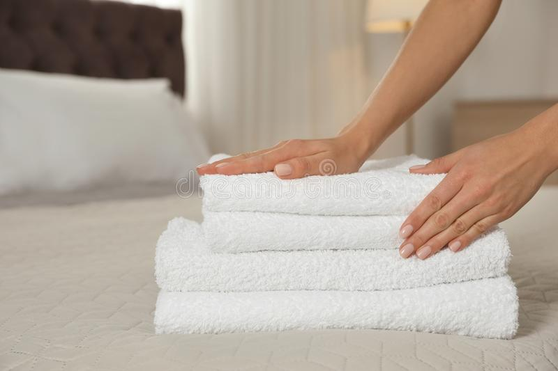 Chambermaid putting fresh towels on bed in hotel room. Space for text stock photography
