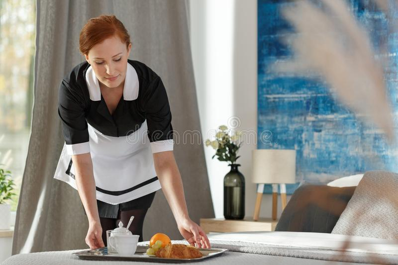 Chambermaid putting tray with fruits royalty free stock image