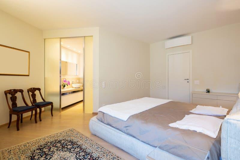 Chambre à coucher élégante en villa moderne photo stock