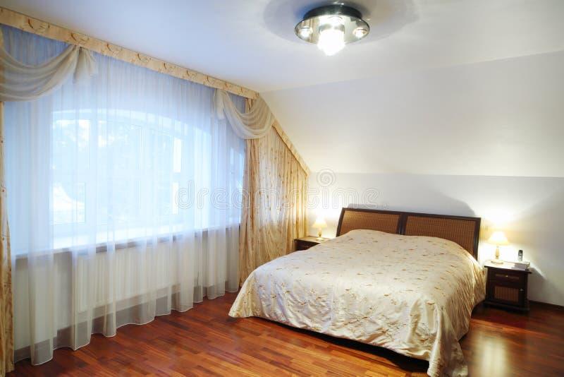 Chambre à coucher avec le beau lit avec des tables de chevet, grande fenêtre images stock