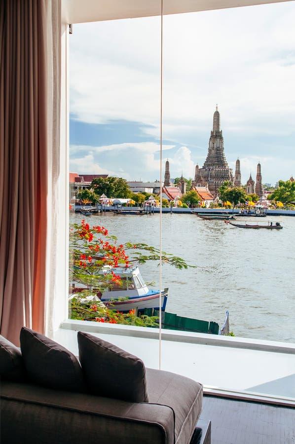 Chambre à coucher avec le divan par la grande fenêtre en saillie avec Wat Arun Temple image stock