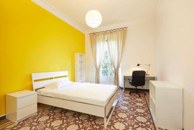 Chambre à coucher avec le grand lit et bureau en appartement rénové photos libres de droits