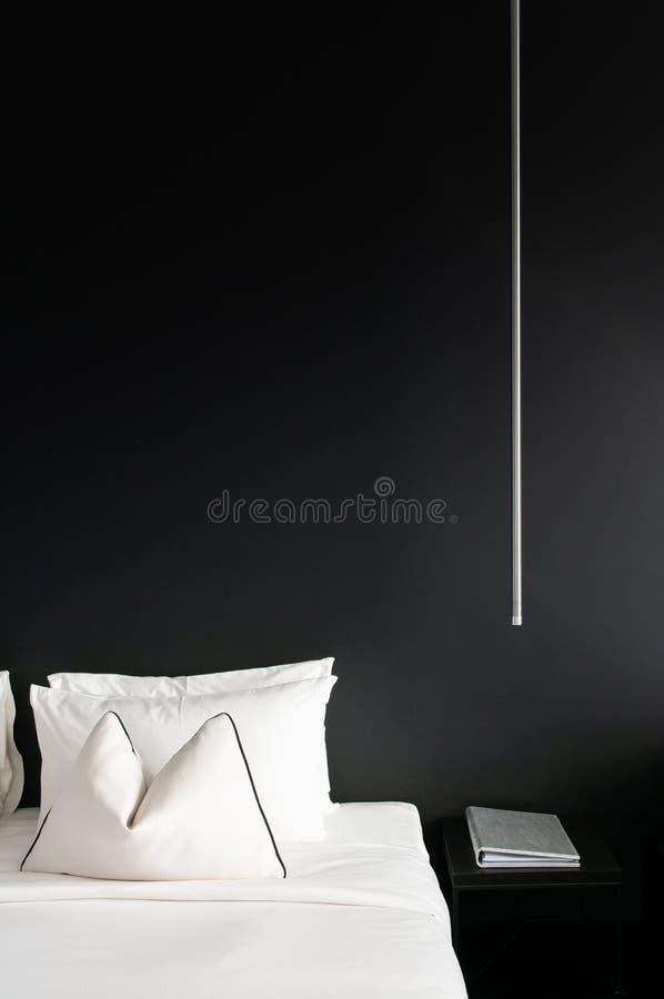 Chambre à coucher avec le lit blanc de mur noir, oreillers table latérale moderne, La photos stock
