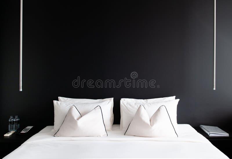 Chambre à coucher avec le lit blanc de mur noir, oreillers table latérale moderne, La photos libres de droits