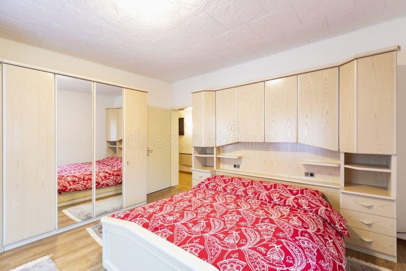 Chambre à coucher avec les couvertures rouges et la garde-robe en bois photographie stock libre de droits