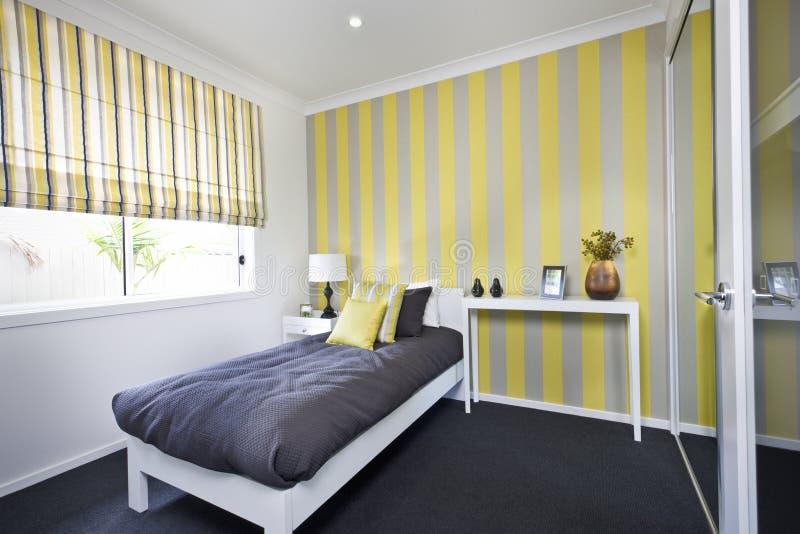 Chambre à coucher classique avec un petit lit et oreillers près des fenêtres photos stock