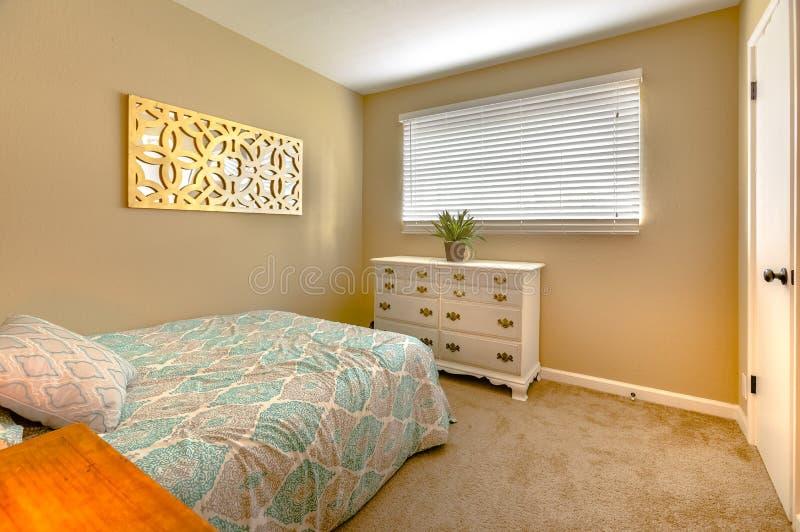 Chambre à coucher confortable avec le lit jumeau, le tapis et l'usine d'intérieur sur la robe images stock