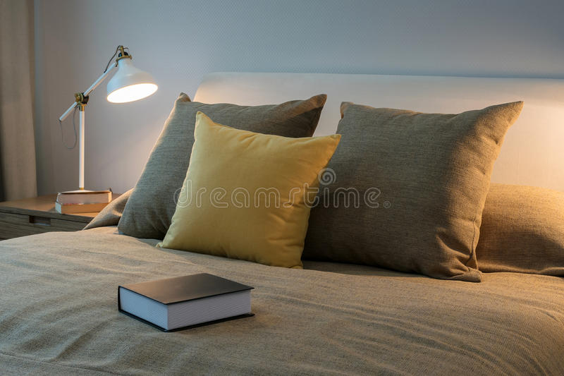 Chambre à coucher confortable avec le livre et la lampe de lecture sur la table de chevet images stock
