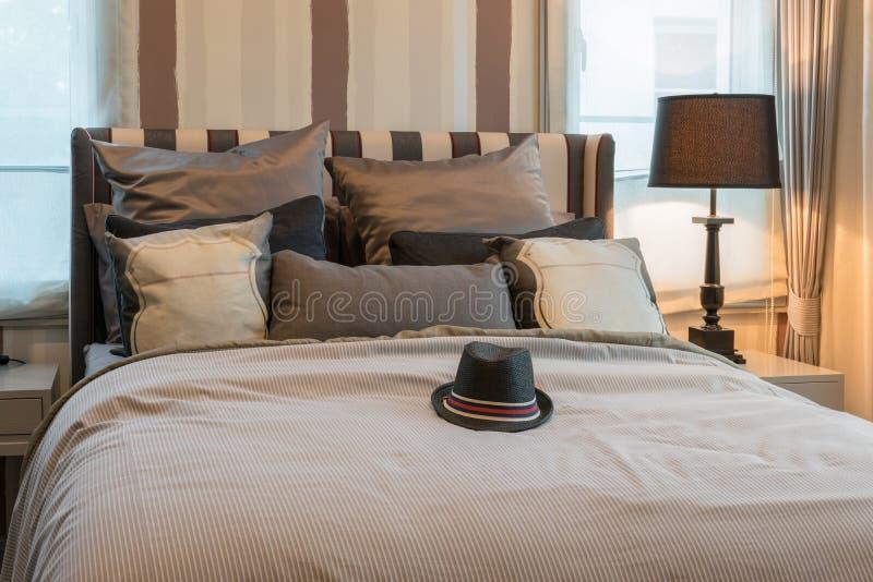 Chambre à coucher confortable avec les oreillers de brun foncé et le chapeau noir sur le lit photos stock