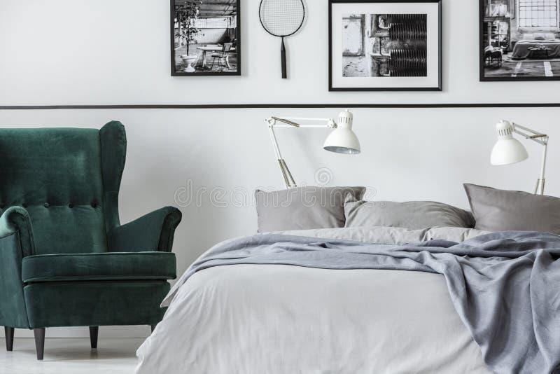 Chambre à coucher de collecteur de photo avec le fauteuil vert et lit grand avec la literie grise image libre de droits