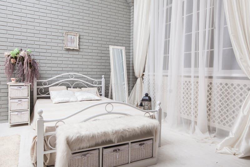 Chambre à coucher de soirée avec un lit blanc, grand miroir près de la fenêtre à image stock