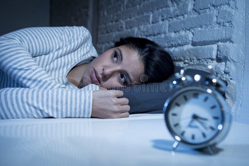 Chambre à coucher hispanique de femme à la maison se situant dans le lit tard la nuit essayant de dormir insomnie de souffrance images stock