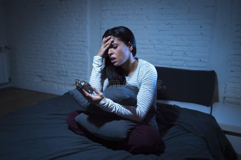 Chambre à coucher hispanique de femme à la maison se situant dans le lit tard la nuit essayant de dormir insomnie de souffrance photographie stock libre de droits