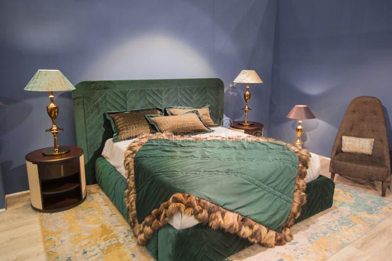 Chambre à coucher à la mode de luxe dans des tons verts et bleu-foncé, avec des tissus de velours et de fourrure Avec des tables  photographie stock