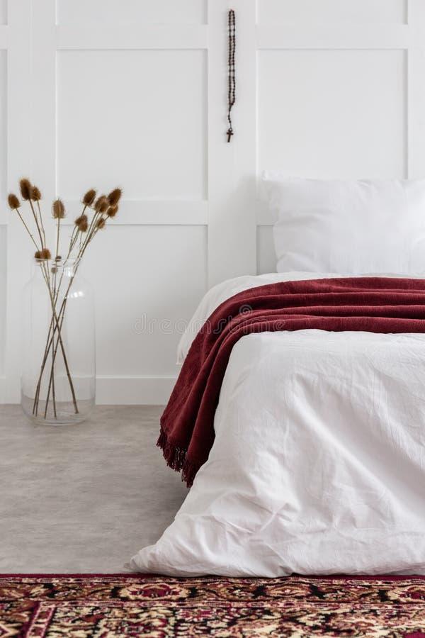 Chambre à coucher minimale blanche avec le lit confortable et couverture rouge là-dessus, vraie photo avec le PS de copie photos stock