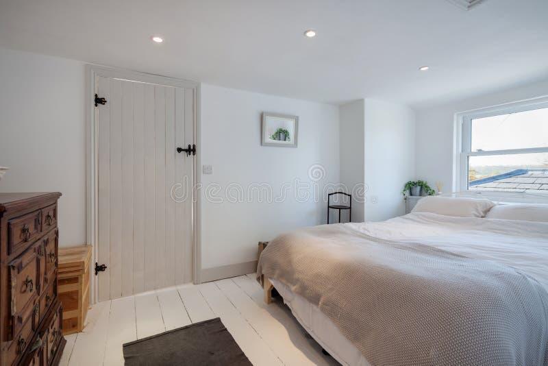 Chambre à coucher minimaliste de cottage décorée dans le blanc images libres de droits
