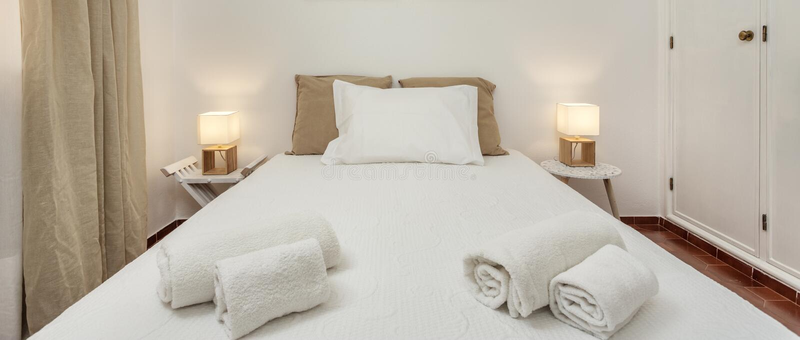 Chambre à coucher moderne avec des oreillers et un lit pour des touristes frontally photo stock