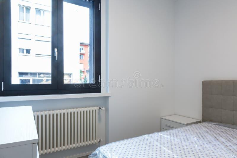 Chambre à coucher moderne avec la grande fenêtre lumineuse photographie stock libre de droits