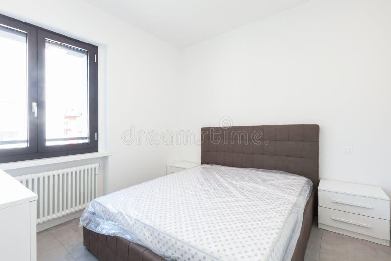 Chambre à coucher moderne avec la grande fenêtre lumineuse photos stock