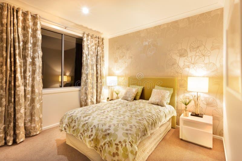 Chambre à coucher moderne avec le lit grand illuminé par des lampes de table photos libres de droits
