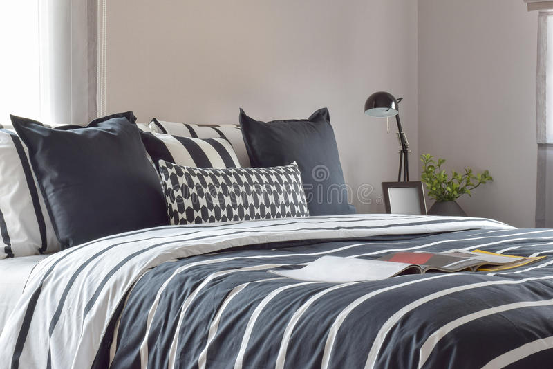 Chambre à coucher moderne avec les oreillers et la lampe de lecture sur la table de chevet photo libre de droits