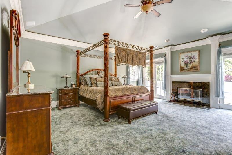 Chambre à coucher principale de luxe avec le lit et la cheminée d'auvent photo libre de droits