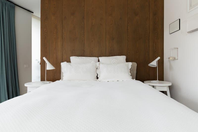 Chambre à coucher principale de luxe avec le panneautage en bois de noix derrière le lit photo stock