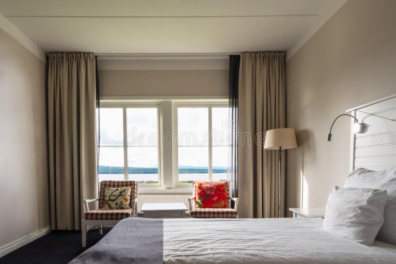Chambre aménagée et aménagée avec grand lit et fauteuils devant deux fenêtres avec vue sur le paysage images stock