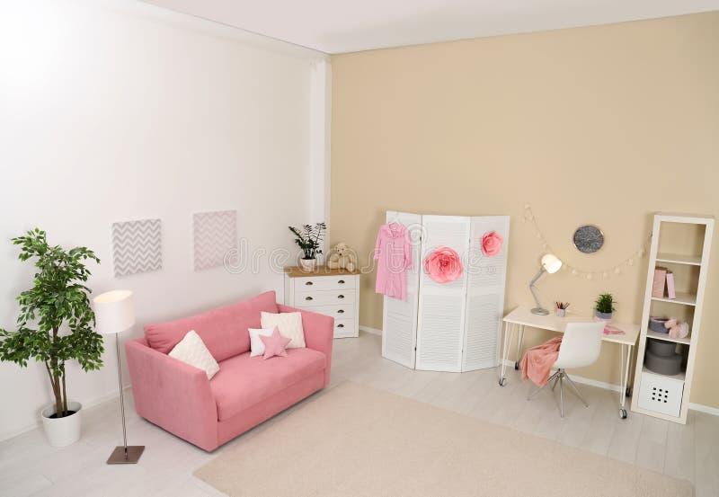 Chambre d'enfant confortable intérieure avec le sofa, station d'étude images stock