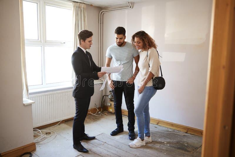 Chambre de achat de couples regardant pour la première fois l'enquête avec l'agent immobilier photos stock