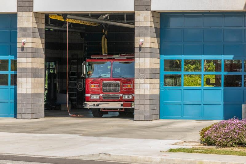Chambre de Firestation avec le firetruck dans la baie ouverte photo libre de droits