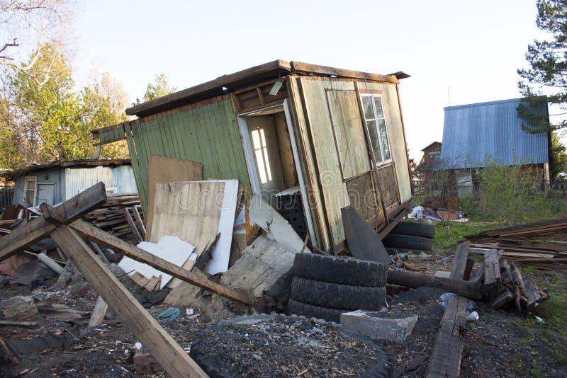 Chambre en bois ruin?e Autour des déchets différents, pneus, panneaux image libre de droits