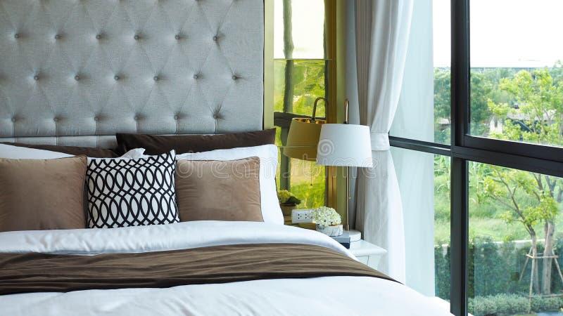 Chambre moderne à côté de la fenêtre le matin, oreillers et coussins dans les tons blanc, beige et marron sur le lit dans la cham image libre de droits