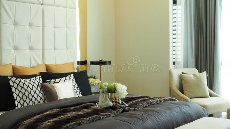 Chambre moderne, plateau de vase avec fleurs sur le lit dans les luxueux tons beiges chambre à la maison photographie stock